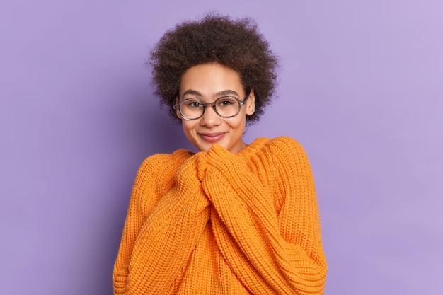 Vrij krullend haar duizendjarige meisje houdt handen in de buurt van kin glimlacht aangenaam hoort iets goeds draagt optische bril oranje gebreide trui.