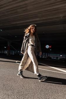 Vrij krullend jong meisje in een modieuze lange jas met een trui, broek en laarzen in de stad in de buurt van de parkeerplaats. casual stijl en schoonheid van stedelijke vrouwen