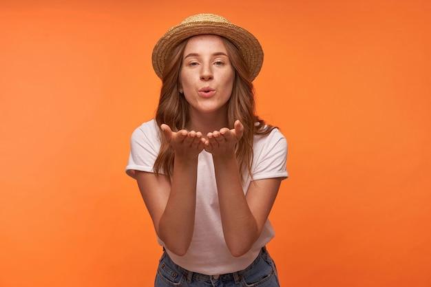 Vrij krullend roodharige vrouw blaast luchtkus, handpalmen omhoog en vouwende lippen in luchtkus, romantische hoed en vrijetijdskleding dragen