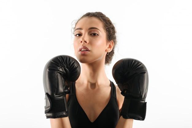 Vrij krullende donkerbruine geschiktheidsvrouw in bokshandschoenen