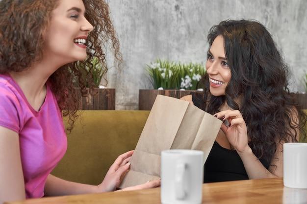 Vrij krullende vrouw die huidig maakt aan vrouwelijke vriend in koffie