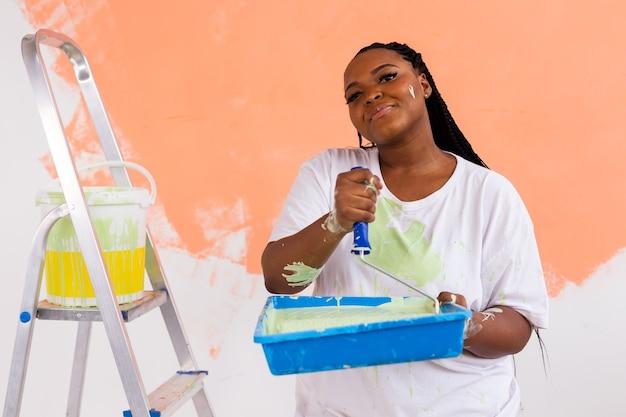 Vrij lachende afro-amerikaanse vrouw schilderij binnenmuur van huis met verfroller. herinrichting