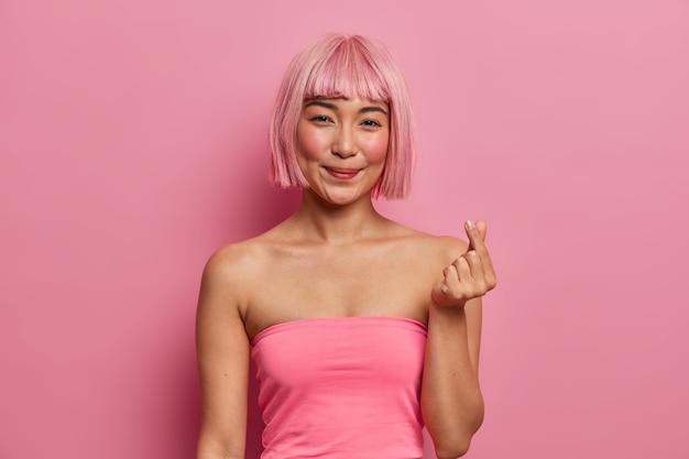 Vrij lachende aziatische dame met bob kapsel, liefde uitdrukt, maakt als gebaar met vingers, roze top draagt