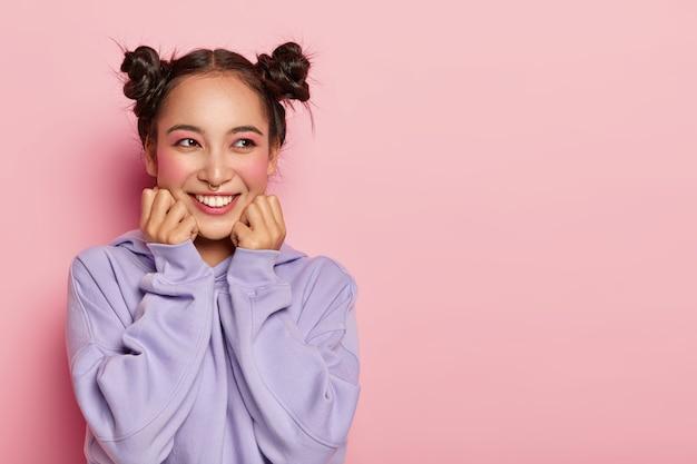 Vrij lachende aziatische vrouw met donker haar, twee knopen, draagt paarse losse trui