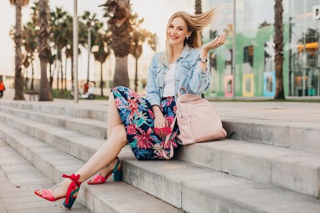 Vrij lachende blonde vrouw zittend op de trap in de stad straat in stijlvolle bedrukte rok en oversized denim jasje met lederen rugzak, zomer stijl trend