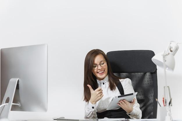 Vrij lachende bruinharige zakenvrouw in pak en bril zittend aan de balie, duim opdagen, werken op computer met moderne monitor met document en tablet in licht kantoor