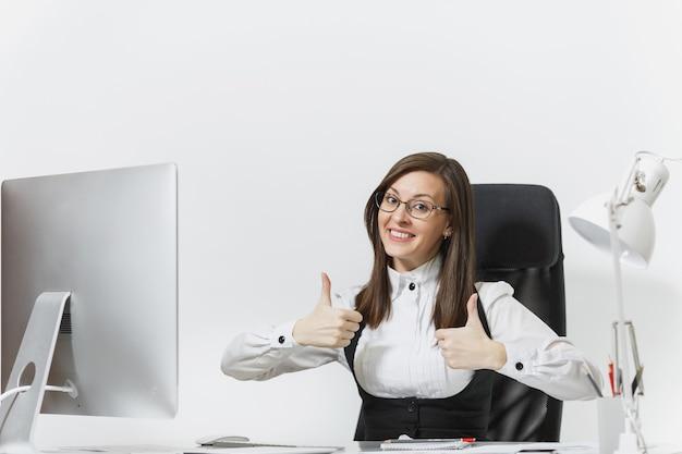Vrij lachende bruinharige zakenvrouw in pak en bril zittend aan een bureau, werkend op de computer met moderne monitor met documenten in een licht kantoor, duim beide handen opdagend