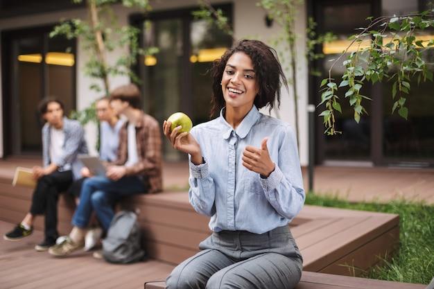 Vrij lachende dame zittend op de bank met groene appel en gelukkig met grote duim omhoog gebaar terwijl