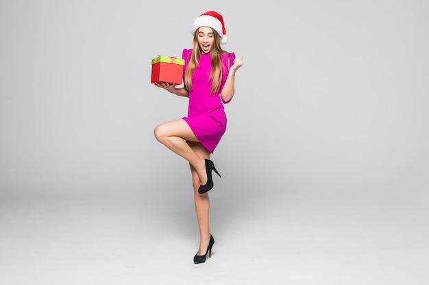 Vrij lachende gelukkige dame in korte roze jurk en nieuwjaarshoed houden papieren doosverrassing in haar handen