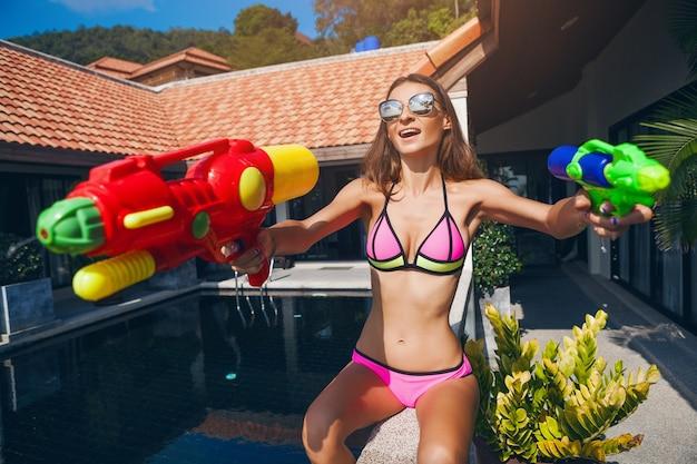 Vrij lachende gelukkige vrouw spelen met watergun speelgoed bij zwembad op tropische zomervakantie op villahotel plezier in bikini zwembroek, kleurrijke stijl, feeststemming