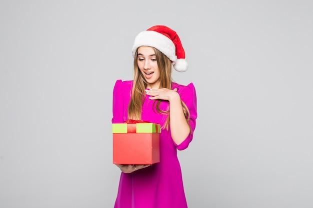 Vrij lachende grappige dame in korte roze jurk en nieuwjaarshoed houden kartonnen doos verrassing in haar handen