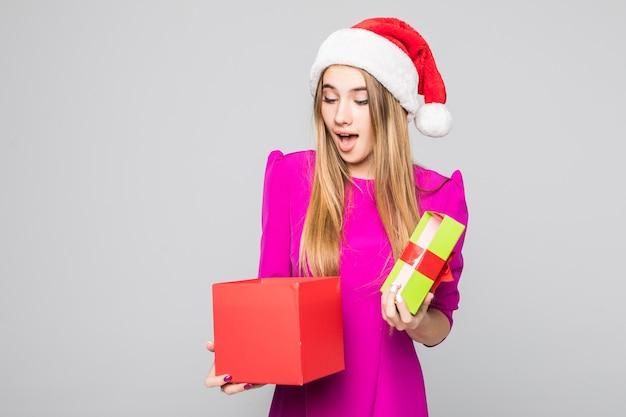 Vrij lachende grappige gelukkige dame in korte jurk en nieuwjaarshoed houden kartonnen doos verrassing in haar handen