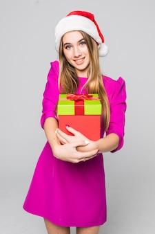 Vrij lachende grappige gelukkige dame in roze jurk en nieuwe jaar hoed houden kartonnen doos verrassing in haar handen