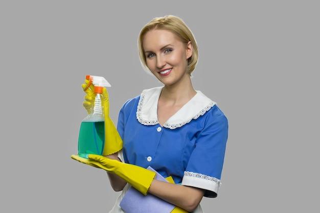 Vrij lachende huishoudster met schoonmaak spray. vrouw reiniger weergegeven: fles afwasmiddel. reclame voor professionele schoonmaakdiensten.