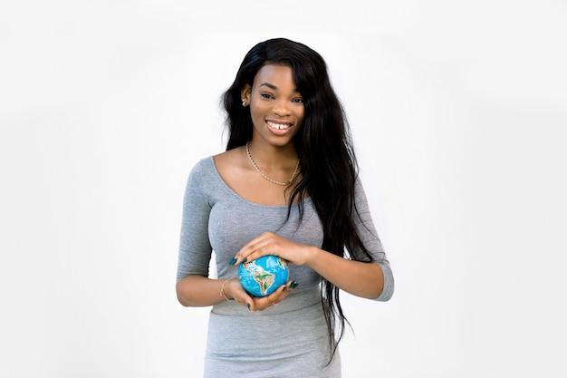 Vrij lachende jonge afro-amerikaanse vrouw in vrijetijdskleding met de kleine aarde-bol in handen