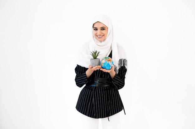 Vrij lachende jonge arabische vrouw in hijab met earth globe planet plant