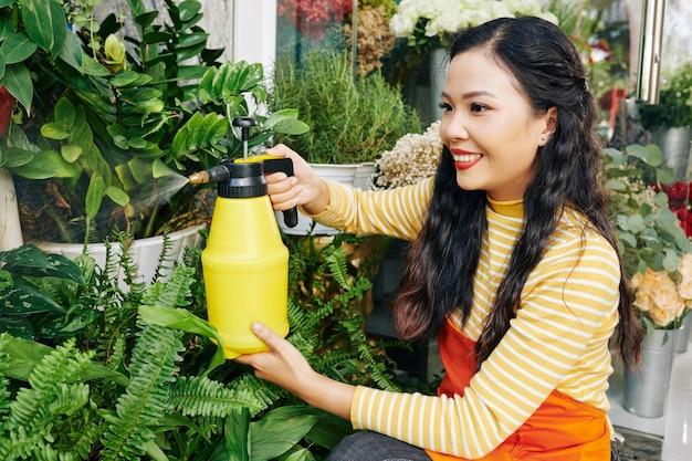 Vrij lachende jonge aziatische bloemist planten en bloemen sproeien in haar winkel
