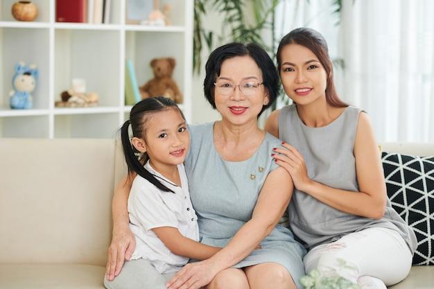 Vrij lachende jonge vrouw en preteen dochter die haar senior moeder thuis bezoekt voor vakantie