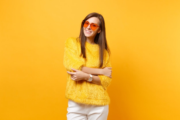 Vrij lachende jonge vrouw in bont trui, witte broek, hart oranje brillen hand in hand gevouwen geïsoleerd op heldere gele achtergrond. mensen oprechte emoties, lifestyle concept. reclame gebied.