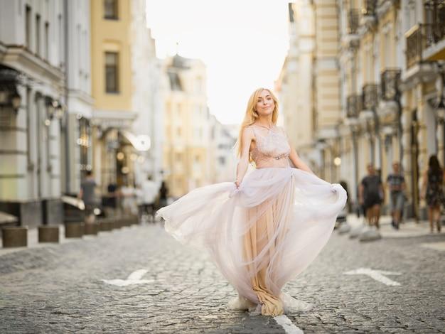 Vrij lachende jonge vrouw met lang blond haar in elegante vliegende lichte jurk die langs de straat loopt