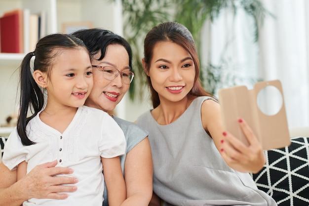 Vrij lachende jonge vrouw met smartphone selfie te nemen met haar senior moeder en dochtertje