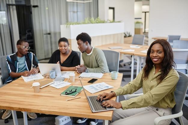 Vrij lachende jonge zwarte zakenvrouw typen op laptop bij het bijwonen van zakelijke bijeenkomst met collega...