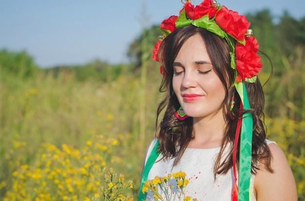 Vrij lachende meisje in een krans van poppy bloemen en nationale geborduurde etnische jurk poseren in de weide van gele veld bloemen verlicht met zomerzon