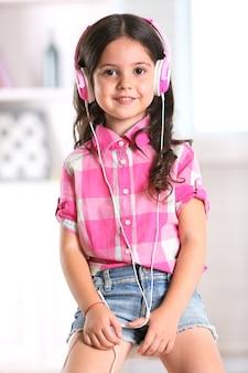 Vrij lachende meisje luisteren muziek met roze koptelefoon in lichte kamer