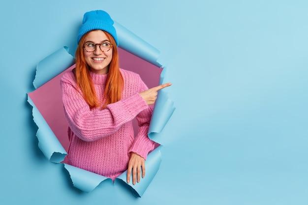 Vrij lachende roodharige vrouw in blauwe hoed en gebreide trui wijst op kopie ruimte