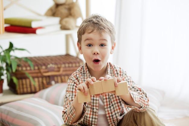 Vrij lachende verraste jongen die thuis met houten kubussen speelt