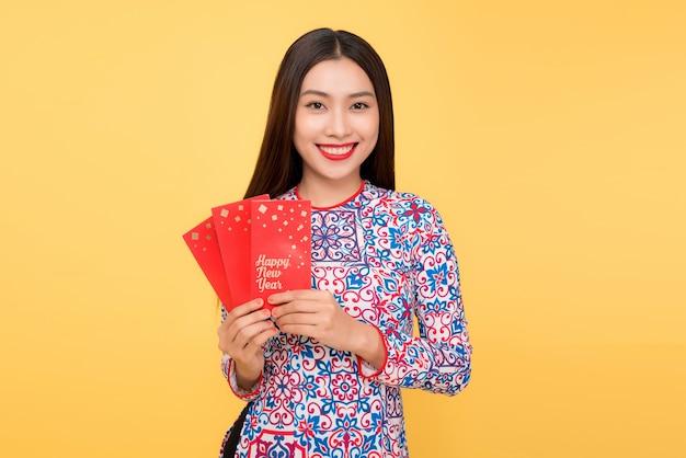 Vrij lachende vietnamese vrouw met rode enveloppen geïsoleerd op gele achtergrond