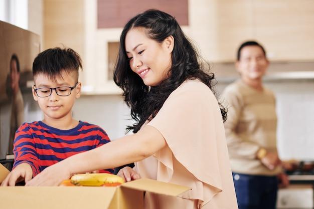 Vrij lachende volwassen vrouw en haar zoon die verse groenten en fruit uit de kartonnen doos nemen