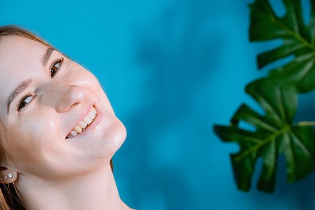 Vrij lachende vreugdevolle vrouw met bruin haar, tevreden kijkend naar de camera, gelukkig. studio shot van knappe mooie vrouw op achtergrond studio muur en tropische bladeren.
