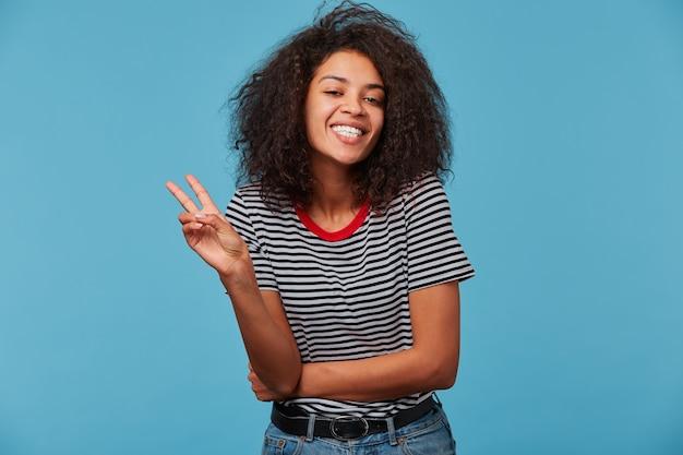 Vrij lachende vrouw met afro kapsel doet vredesteken met hand