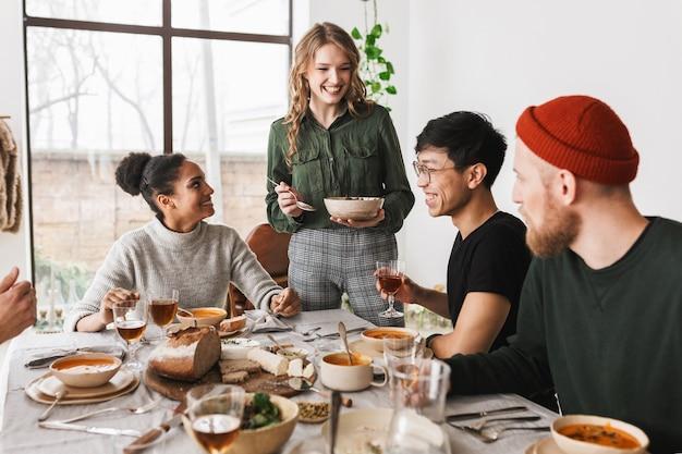 Vrij lachende vrouw met kom met salade in de hand gelukkig tijd doorbrengen met collega's