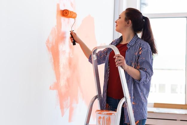 Vrij lachende vrouw schilderij binnenmuur van huis met verfroller. herinrichting, renovatie