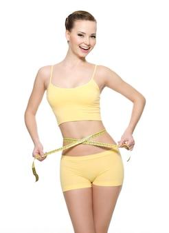 Vrij lachende vrouw taille meten met type meting geïsoleerd op wit
