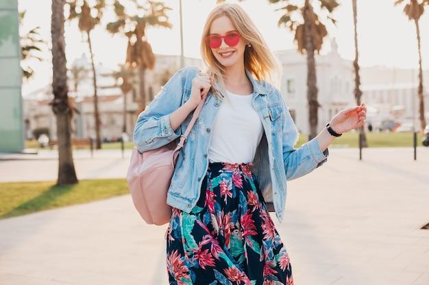 Vrij lachende vrouw wandelen in de stad straat in stijlvolle bedrukte rok en oversized denim jasje roze zonnebril, zomer stijl trend