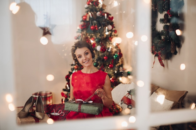 Vrij lachende vrouw zit in haar slaapkamer met kerstcadeau