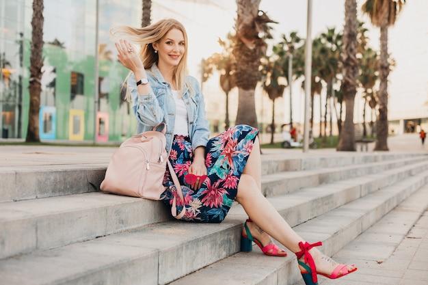 Vrij lachende vrouw zittend op de trap in de stad straat in stijlvolle bedrukte rok en oversized denim jasje met lederen rugzak, zomer stijl trend