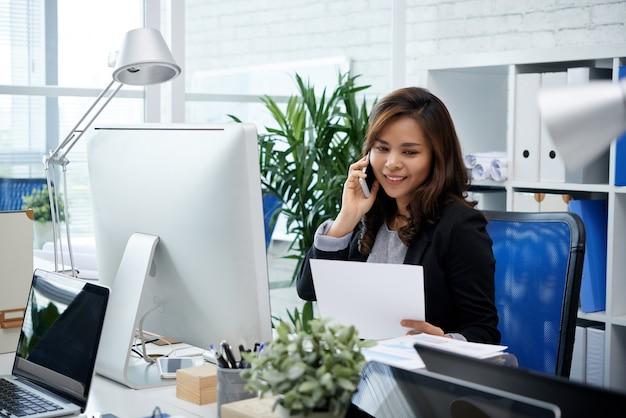 Vrij lachende vrouwelijke ondernemer die aan de telefoon praat met een collega van een andere afdeling als hij kijkt...