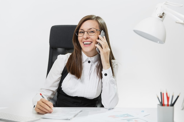Vrij lachende zakenvrouw in pak zittend aan de balie, werken op hedendaagse computer met document in licht kantoor, praten op mobiele telefoon, aangenaam gesprek voeren