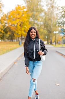 Vrij lachende zwarte meid met trendy vrijetijdskleding met een mode-jas, jeans en een stijlvolle handtas loopt in een herfstpark met felgeel herfstgebladerte