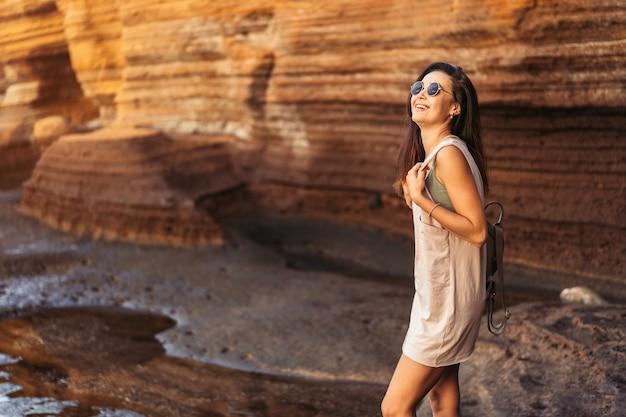 Vrij lang haar brunette toeristische meisje ontspannen op de stenen in de buurt van zee.