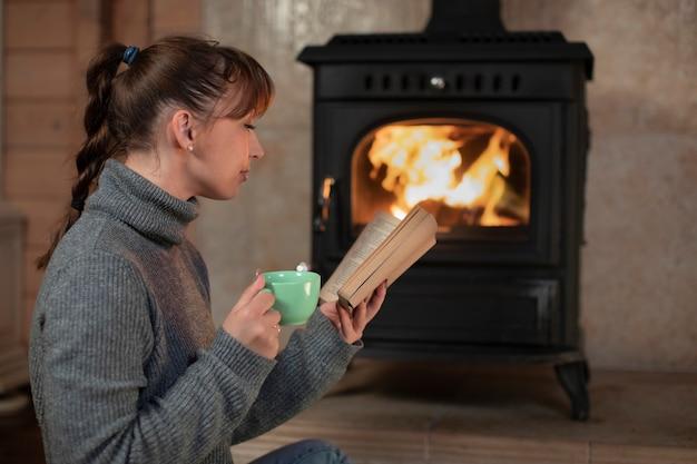 Vrij lang haar donkerbruine vrouw met draadantenne in grijze sweaterlezing bij open haard met kop in haar hand