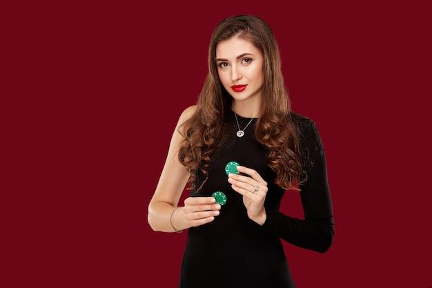 Vrij langharige vrouw in zwarte jurk met fiches om te gokken