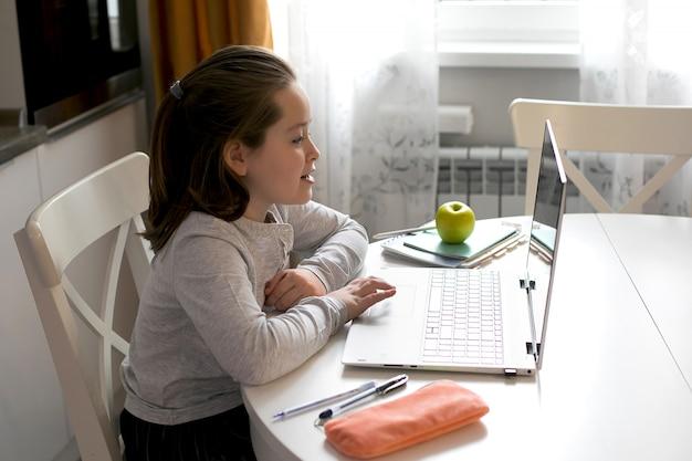 Vrij leuk schoolmeisje dat thuis met behulp van laptop bestudeert.
