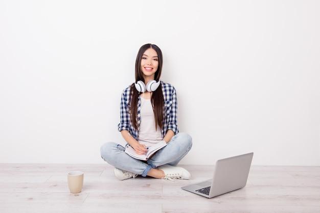 Vrij leuke jonge vrouwelijke student luisteren muziek maakt gebruik van een computer en koffie drinken