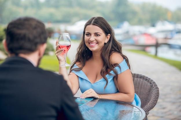 Vrij leuke lachende vrouw in blauwe jurk en man met glazen wijn op terras