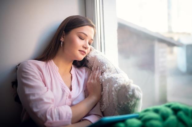 Vrij leuke vrouw die tijdens het slapen tegen het raam leunt